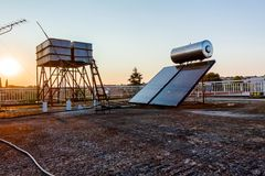 Los paneles solares y el tanque viejo del metal, calentador de agua en el tejado, verde foto de archivo libre de regalías