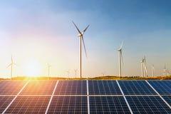 los paneles solares y turbina de viento con puesta del sol en la colina Concepto i foto de archivo