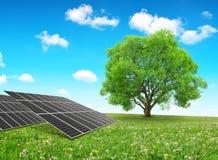 Los paneles y árbol de energía solar en prado Imagenes de archivo