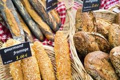 Los panes franceses con precio genérico firman en el paño comprobado rojo en mercado francés Imagen de archivo