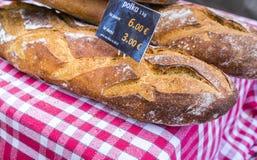 Los panes franceses con precio genérico firman en el paño comprobado rojo en mercado francés Fotografía de archivo