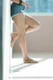 Los pantalones cortos atractivos largos de los vaqueros de las mujeres de la pierna forman la situación a la pared Fotos de archivo