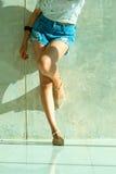 Los pantalones cortos atractivos largos de los vaqueros de las mujeres de la pierna forman la situación a la pared Imagen de archivo
