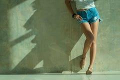 Los pantalones cortos atractivos largos de los vaqueros de las mujeres de la pierna forman la situación a la pared Fotografía de archivo libre de regalías