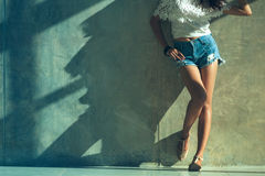 Los pantalones cortos atractivos largos de los vaqueros de las mujeres de la pierna forman la situación a la pared Fotografía de archivo
