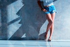 Los pantalones cortos atractivos largos de los vaqueros de las mujeres de la pierna forman la situación a la pared Imagen de archivo libre de regalías