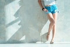 Los pantalones cortos atractivos largos de los vaqueros de las mujeres de la pierna forman la situación a la pared Imágenes de archivo libres de regalías