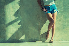 Los pantalones cortos atractivos largos de los vaqueros de las mujeres de la pierna forman la situación a la pared Foto de archivo