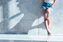 Los pantalones cortos atractivos largos de los vaqueros de las mujeres de la pierna forman la situación a la pared Fotos de archivo libres de regalías