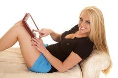 Los pantalones cortos azules largos del pelo rubio de la mujer celebran mirada de la tableta Imagen de archivo libre de regalías