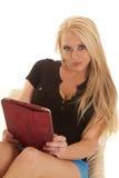 Los pantalones cortos azules largos del pelo rubio de la mujer celebran mirada de la tableta seria Foto de archivo
