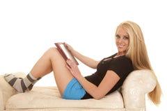Los pantalones cortos azules largos del pelo rubio de la mujer celebran sonrisa de la tableta Fotografía de archivo libre de regalías