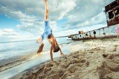 Los pantalones cortos del muchacho son saltos felices y mueven de un tirón en la playa Imagenes de archivo