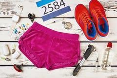 Los pantalones cortos, las zapatillas de deporte y el ` s del corredor numeran imágenes de archivo libres de regalías