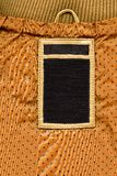 Los pantalones vaqueros etiquetan en la materia textil punteada amarilla Imagenes de archivo