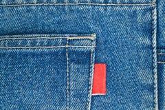 Los pantalones vaqueros viejos azules embolsan con la escritura de la etiqueta roja vacía Foto de archivo