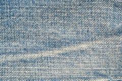 Los pantalones viejos superficiales de la mezclilla del primer texturizaron el fondo fotos de archivo