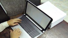Los papeles caen, trabajando en el ordenador portátil con el documento