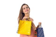 Los paquetes brillantes grandes delanteros de los estiramientos de la muchacha con los regalos se aíslan en un fondo blanco Foto de archivo