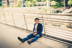 Los parados del hombre de negocios de la compañía que se sienta en la calle, él es sensación de subrayado y tristeza Fotos de archivo libres de regalías