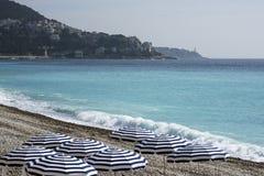 Los paraguas azules, tablas reservadas con los manteles blancos en el Pebble Beach de Promenade des Anglais en Niza, Francia, agu fotos de archivo libres de regalías