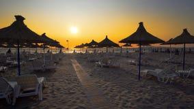 los paraguas están cercanos en la playa contra puesta del sol Imagenes de archivo