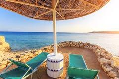 Los paraguas y dos deckchairs vacíos en la arena de la orilla varan Foto de archivo