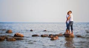 Los pares abrazan en una piedra en el mar Fotografía de archivo