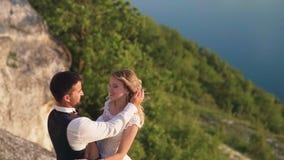 Los pares abrazan suavemente la colocaci?n al borde del acantilado y la mirada en el lago almacen de video