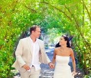 Los pares acaban de casar el funcionamiento feliz en parque verde Imagen de archivo libre de regalías