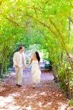Los pares acaban de casar el funcionamiento feliz en parque verde Imágenes de archivo libres de regalías