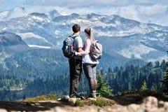 Los pares activos jovenes que caminan en montañas en montañas acercan a marmota fotografía de archivo