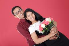 Los pares adolescentes asiáticos románticos sonríen y presentan con el abrazo íntimo Foto de archivo