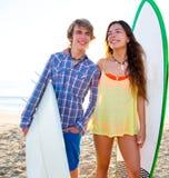 Los pares adolescentes de la persona que practica surf en la playa apuntalan con los tableros de resaca Imagen de archivo libre de regalías