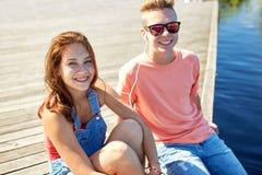 Los pares adolescentes felices con los auriculares en el río atracan Fotos de archivo