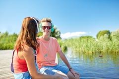 Los pares adolescentes felices con los auriculares en el río atracan Foto de archivo libre de regalías