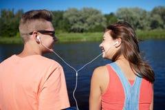 Los pares adolescentes felices con los auriculares en el río atracan Foto de archivo