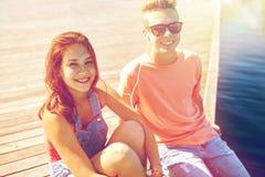 Los pares adolescentes felices con los auriculares en el río atracan Imágenes de archivo libres de regalías