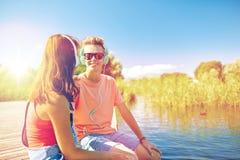 Los pares adolescentes felices con los auriculares en el río atracan Imagenes de archivo