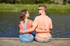 Los pares adolescentes felices que abrazan el verano del río atracan Foto de archivo