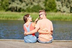 Los pares adolescentes felices que abrazan el verano del río atracan Fotos de archivo