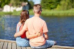 Los pares adolescentes felices que abrazan el verano del río atracan Fotografía de archivo