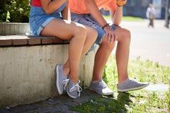 Los pares adolescentes felices que se sientan en la calle de la ciudad bench Fotografía de archivo libre de regalías