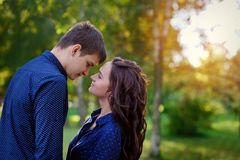Los pares adolescentes jovenes cariñosos que abrazaban con los ojos se cerraron al aire libre Imagenes de archivo