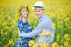 Los pares adultos jovenes felices en la primavera amarillean el campo Foto de archivo