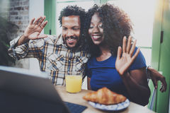 Los pares afroamericanos felices están teniendo conversación en línea junto vía la tableta de tacto en la mañana en sala de estar fotos de archivo