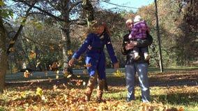 Los pares alegres con el bebé lanzan las hojas otoñales en parque hermoso 4K metrajes