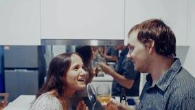 Los pares alegres jovenes atractivos se divierten que baila y cantando con la cucharón bebe el vino mientras que cocina en la coc almacen de video