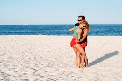 Los pares alegres jovenes felices juntos durante vacaciones de verano vacation en la playa tropical Foto de archivo libre de regalías
