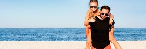 Los pares alegres jovenes felices juntos durante vacaciones de verano vacation en la playa tropical Imagen de archivo libre de regalías